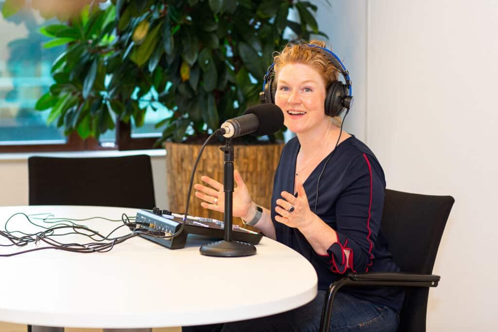 Bianca Groot achter de microfoon voor een podcast