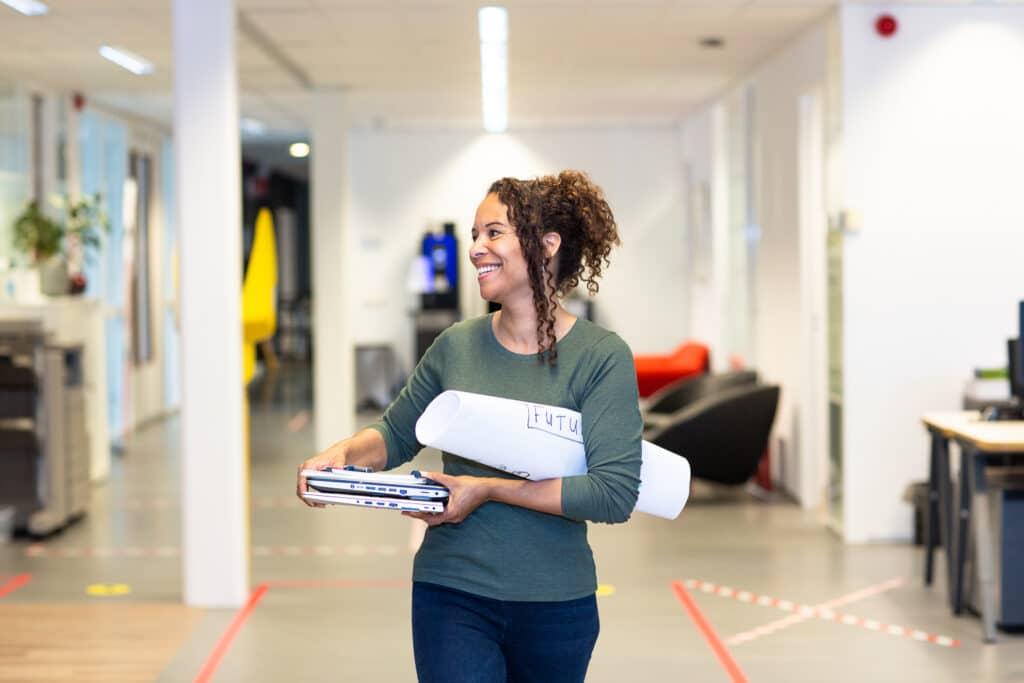 Vrouw loopt met laptops en papieren door kantoor
