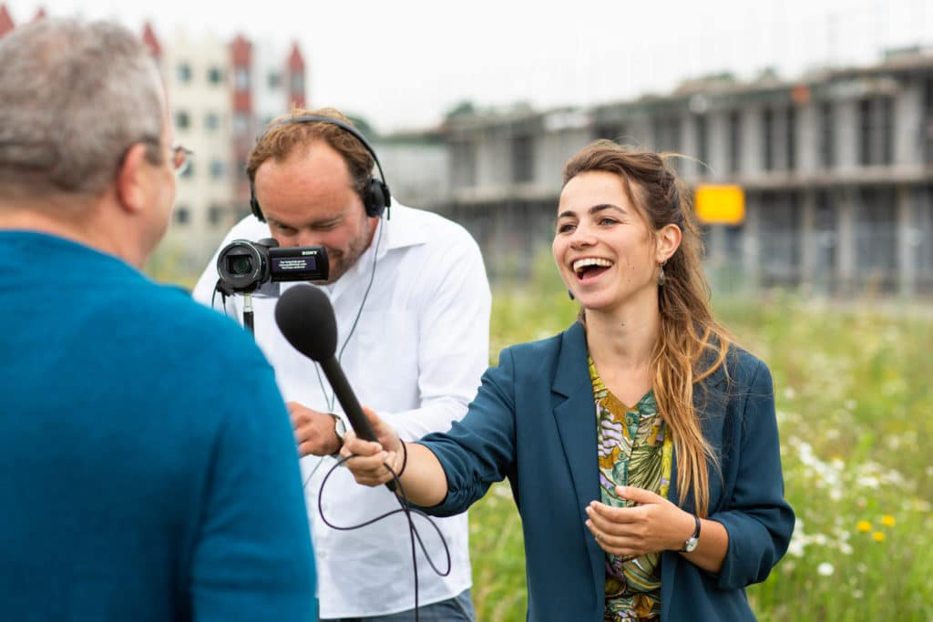 Vrouw met microfoon en man met camera interviewen man