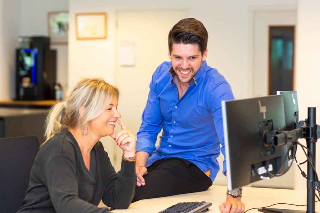 Man en vrouw aan bureau, lachend