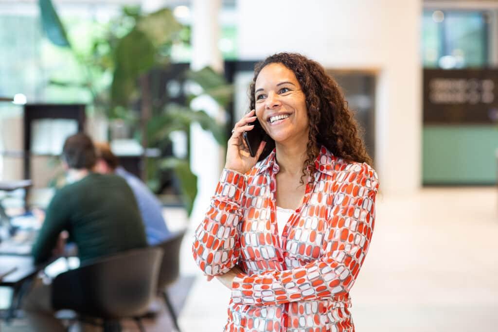 Vrouw lachend aan de telefoon