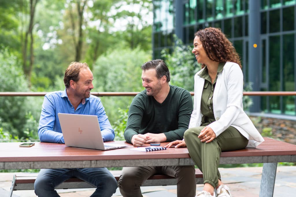 Drie collega's praten met elkaar