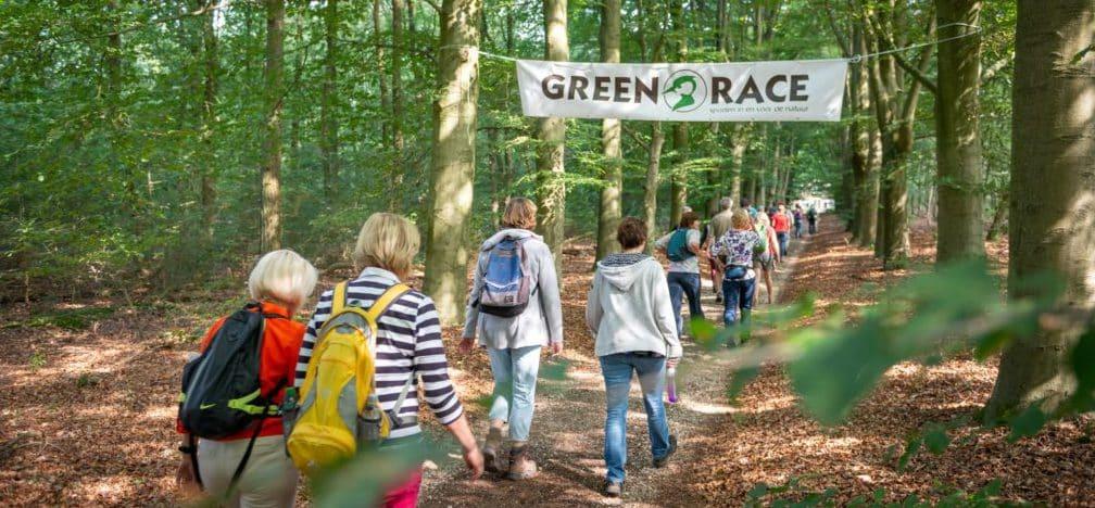 Mensen wandelen in park onder banner van Green Race door